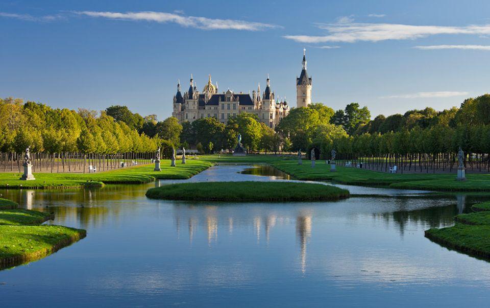 """REISETIPPS: Das Schweriner Schloss thront auf einer Insel und ist auf der UNESCO Anwärterliste zum Welterbe zu finden, denn es ist ein herausragendes Zeugnis des """"Romantischen Historismus"""" des 19. Jahrhunderts. Grund genug es jetzt schon zu besuchen, bevor es der Rest der Welt entdeckt"""
