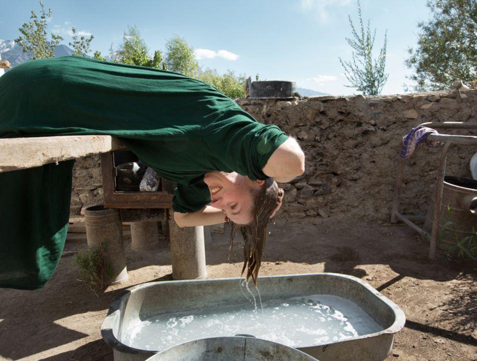 Abenteuer: Stefanie Kicherer wäscht sich im Hof die Haare. Diese Wanne darf nur für die Körperpflege benutzt werden, andere Gefäße nur zum Kochen. Solche Regeln erforscht – und befolgt – sie mit Hingabe