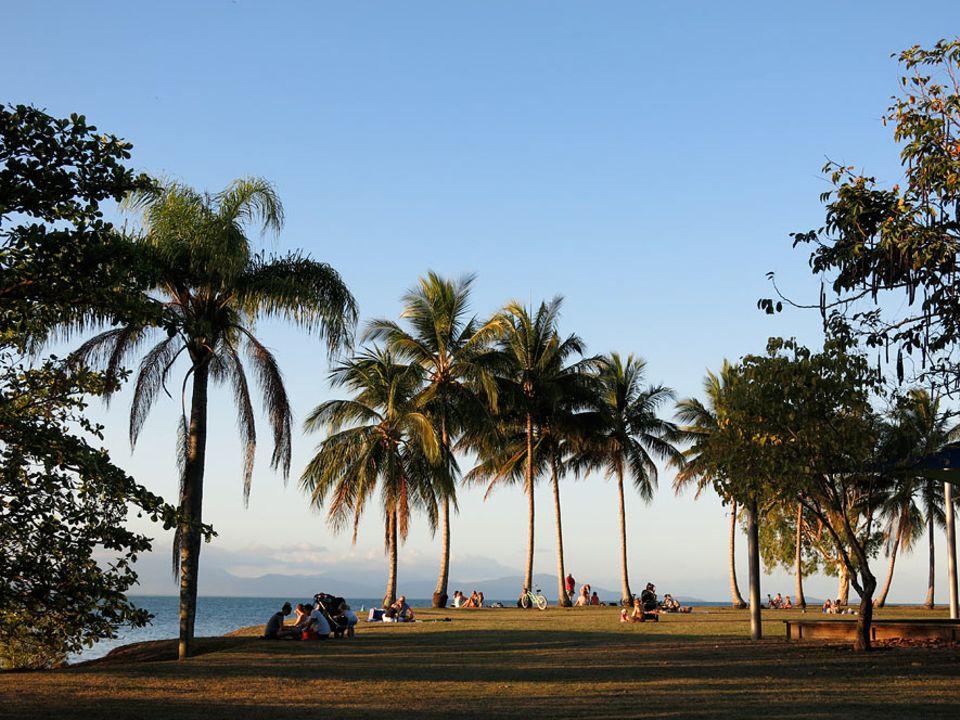 Australiens Ostküste: Backpacker und Einheimische erwarten im Anzac Park von Port Douglas den Sonnenuntergang mit Blick über das Korallenmeer