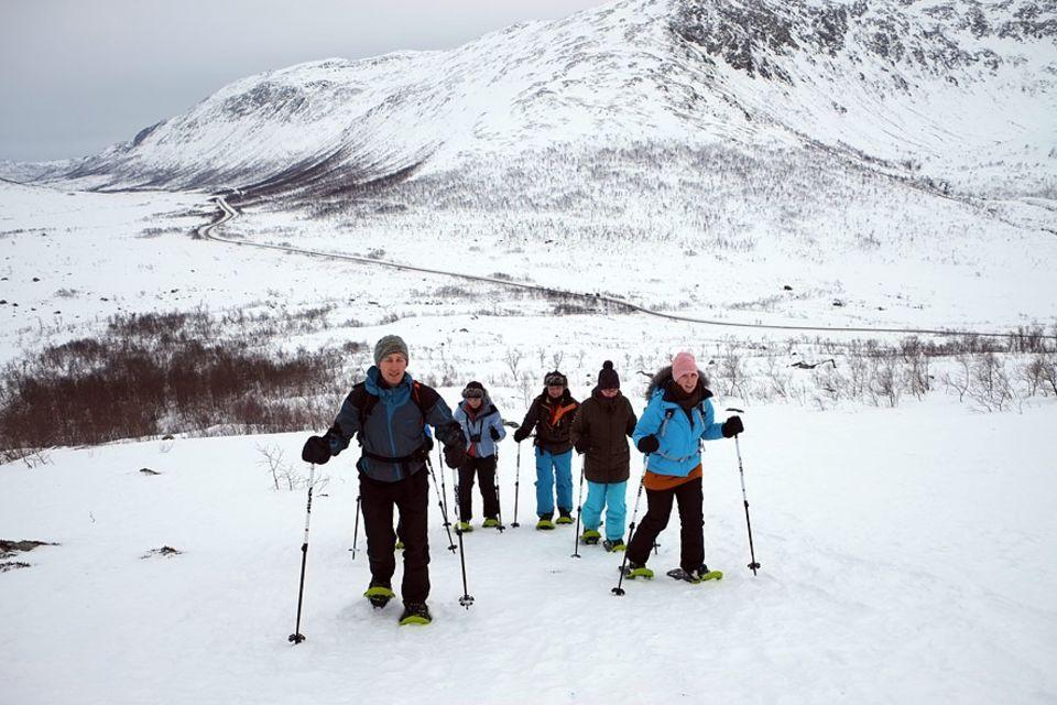 Polarlichter: Bei Wind und Wetter stapft Magne Aarbø mit Schneeschuhen und Gruppe dem Gipfel entgegen. Zur Belohnung hält er oben warmen Tee und lokales Gebäck bereit