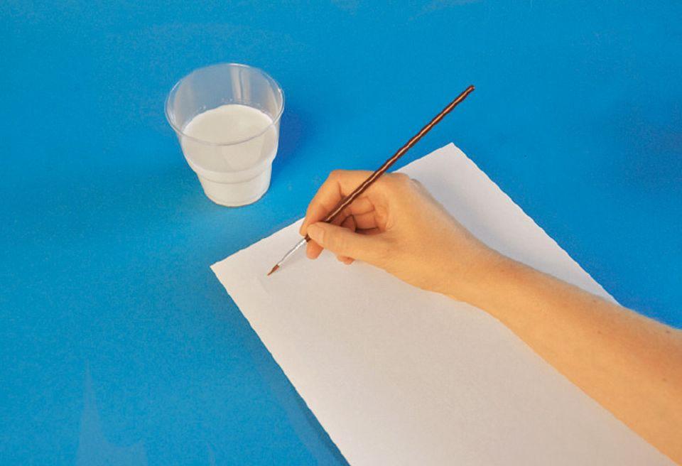 """Verschlüsselte Botschaften: Tunkt den Pinsel in die Milch und schreibt los. Ihr müsst zum Schreiben immer wieder """"Milch-Tinte"""" nachnehmen"""