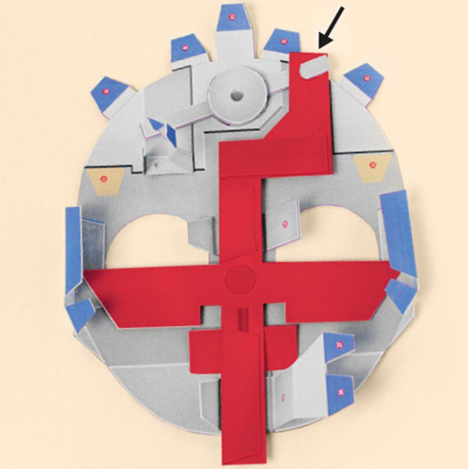 Basteltipp: Verklebt die Zahlen 14 bis 17 miteinander. Setzt auch dieses Teil vorsichtig ein. Fädelt dazu nun die STANGE oben links durch das Loch.