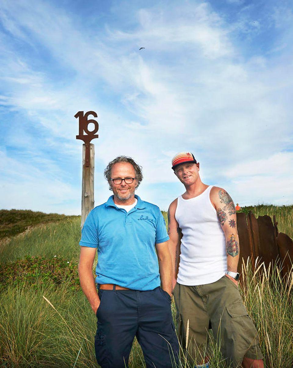 Sylt: Die Behrens-Cousins vor dem angerosteten Erkennungszeichen ihres Strandbistros nördlich von Kampen