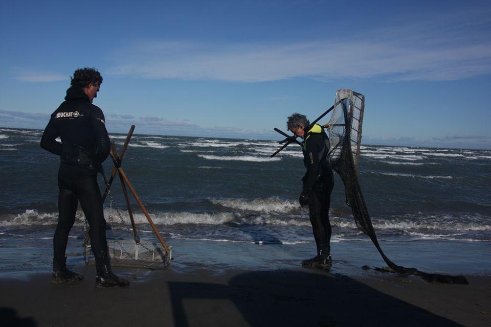 Philippe Rollin re. und Bruno Beusse sind professionelle Tellmuschelfischer. Sie trotzen mit ihren Keschern und auf dem Rücken mit Blei beschwert dem hinterlistigen Mittelmeer an den Küsten der Camargue.