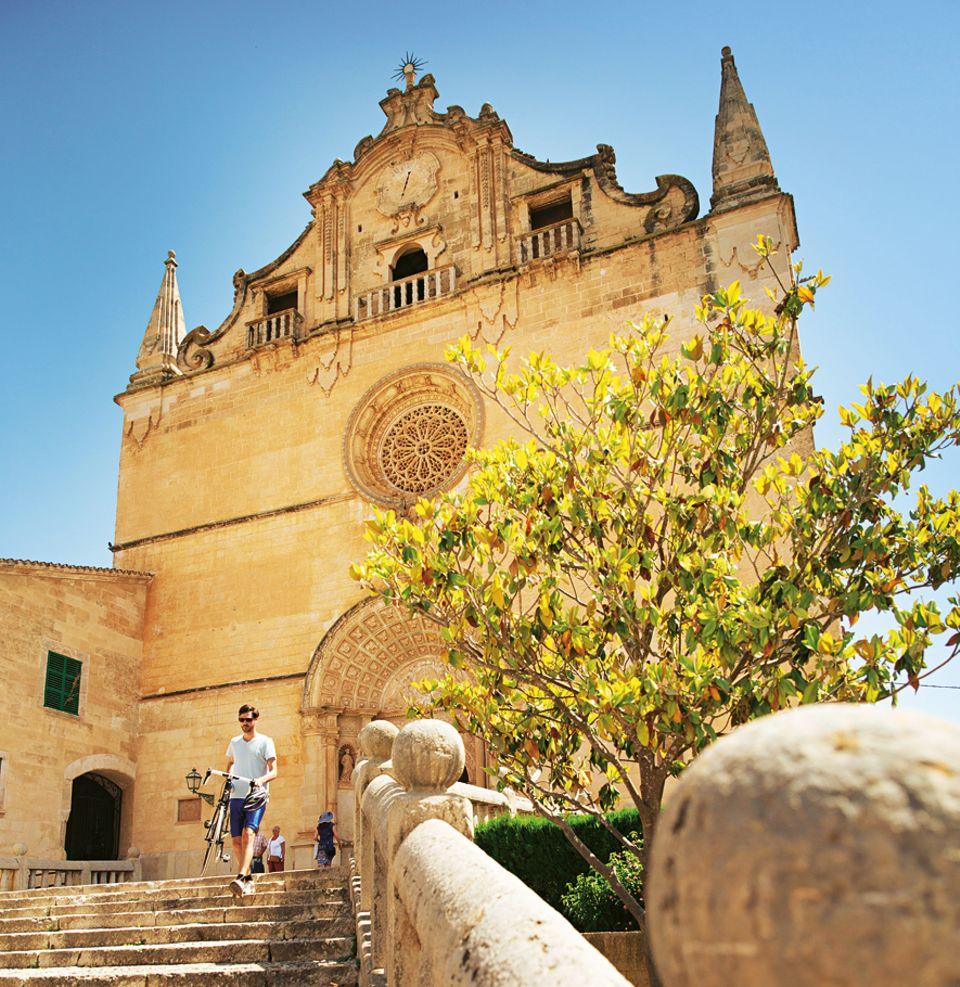Service: Schleppen, strampeln, staunen: Vor der Kirche Sant Miquel in Felanitx trägt der Radler sein Gefährt die Stufen hinunter