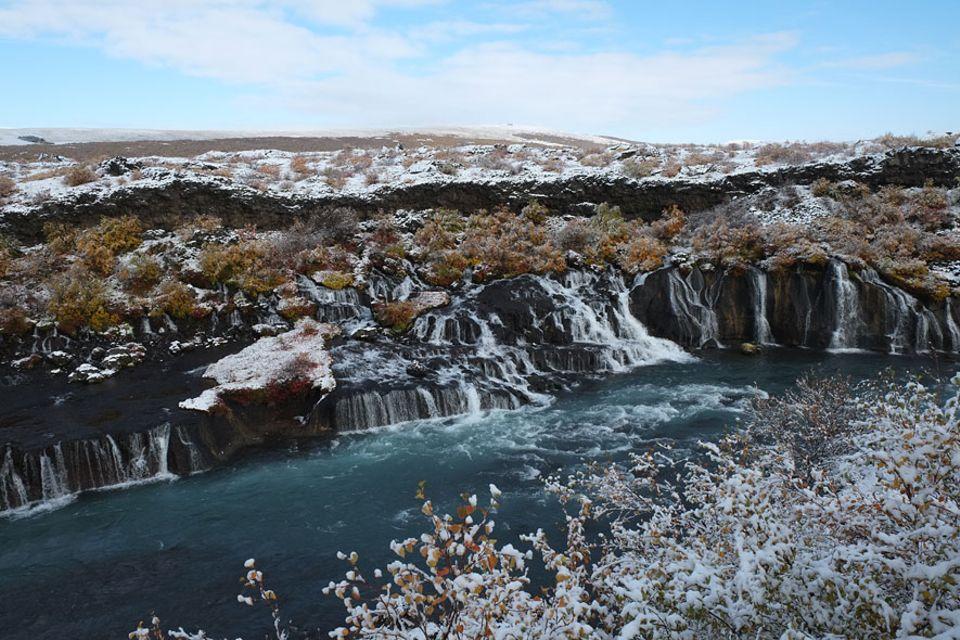 Islands Westen: Auf einer Länge von fast 700 Meter kommt das Wasser am Hraunfossar in Hunderten kleinen Wasserfällen aus dem porösen Lavagestein