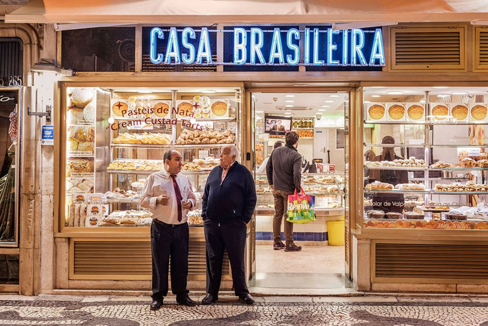 Reisetipps: Ihre geliebten Naschereien lassen die Lissabonner auch nach Sonnenuntergang nicht aus den Augen. Wie hier beim Casa Brasileira trifft man sich zum Plausch
