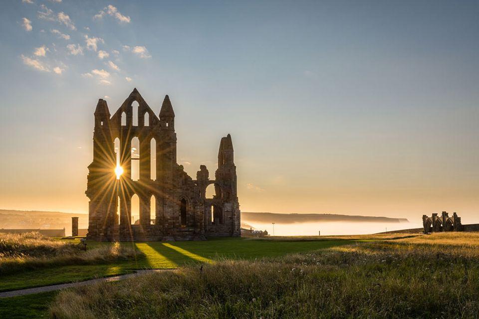 Nordengland: Die ikonische Ruine von Whitby Abbey liegt auf einem Felsen über dem Hafenstädtchen Whitby von dem aus einst Captain Cook in See stach