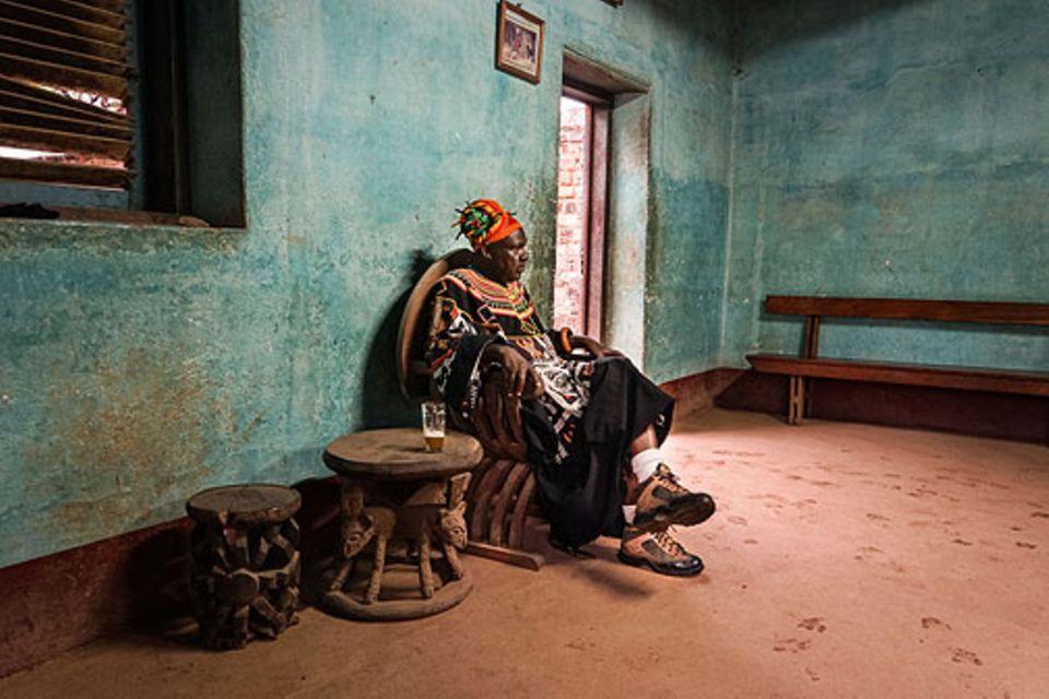 Bafut: Der traditionell gekleidete König auf seinem Thron in einem der Gebäude des Palastes. Insgesamt ist er mit acht Frauen verheiratet und ist eines von rund 300 Geschwistern