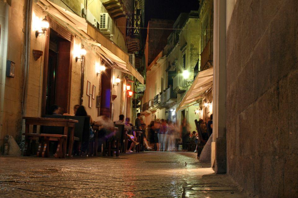 Apulien: Besonders in den kleinen Seitenstraßen geht es in den Abendstunden gemütlich zu. Nach dem Essen kommt der Wein und dann der Tanz