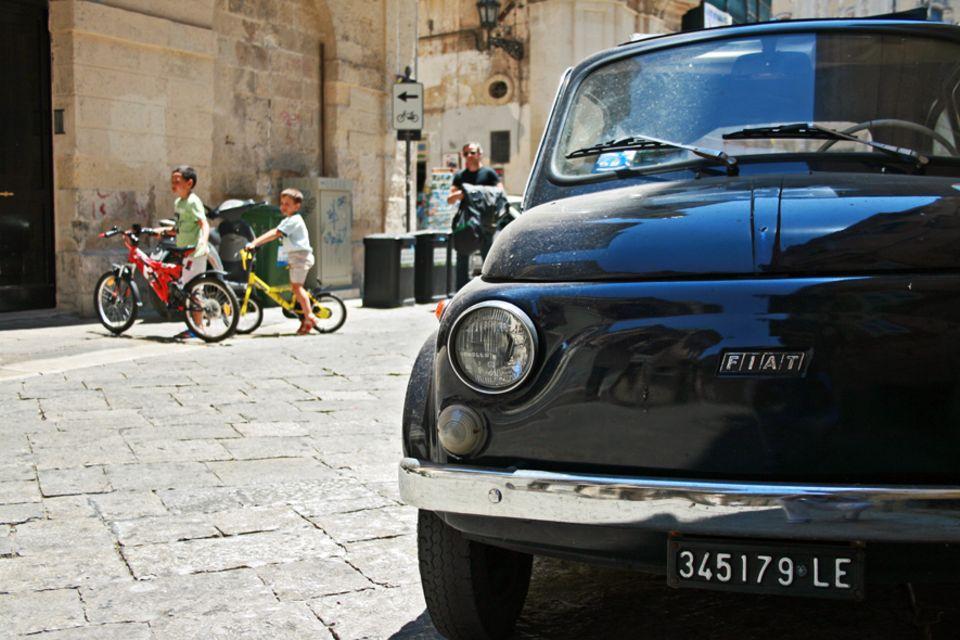 Apulien: Italienisches Straßenbild wie es im Buche steht, mit einem alten Fiat im Fokus