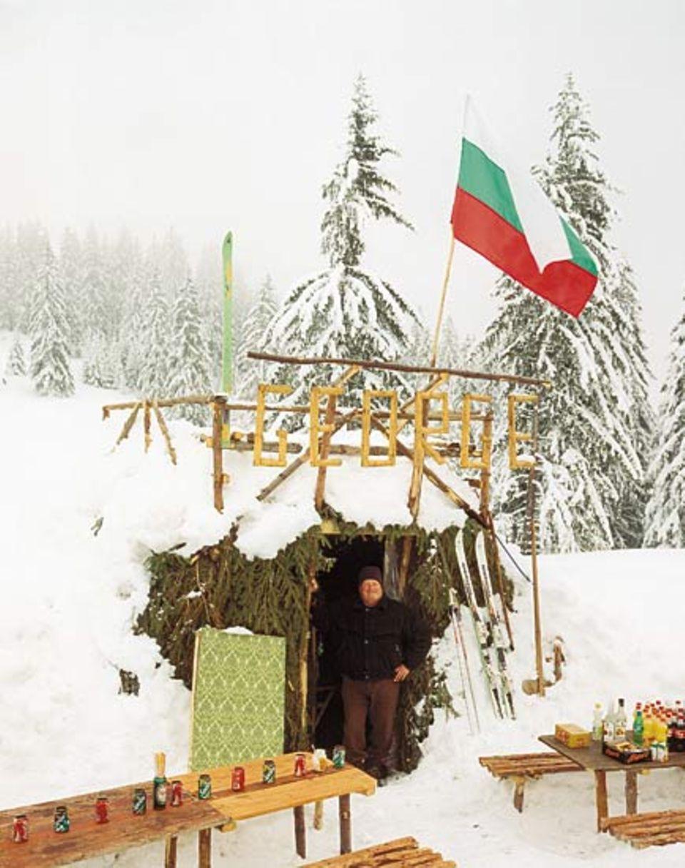 Ein Mann und seine Hütte: George ist Rentner und betreibt im Winter in Borovez eine - Jausenstation? Ski-Bar? Imbissbude? Akkurat hat er leere Dosen als Aschenbecher aufgereiht, stolz die bulgarische Flagge aufgezogen. Seine Spezialität zum Après-Ski: dampfender Kräutertee mit Honig