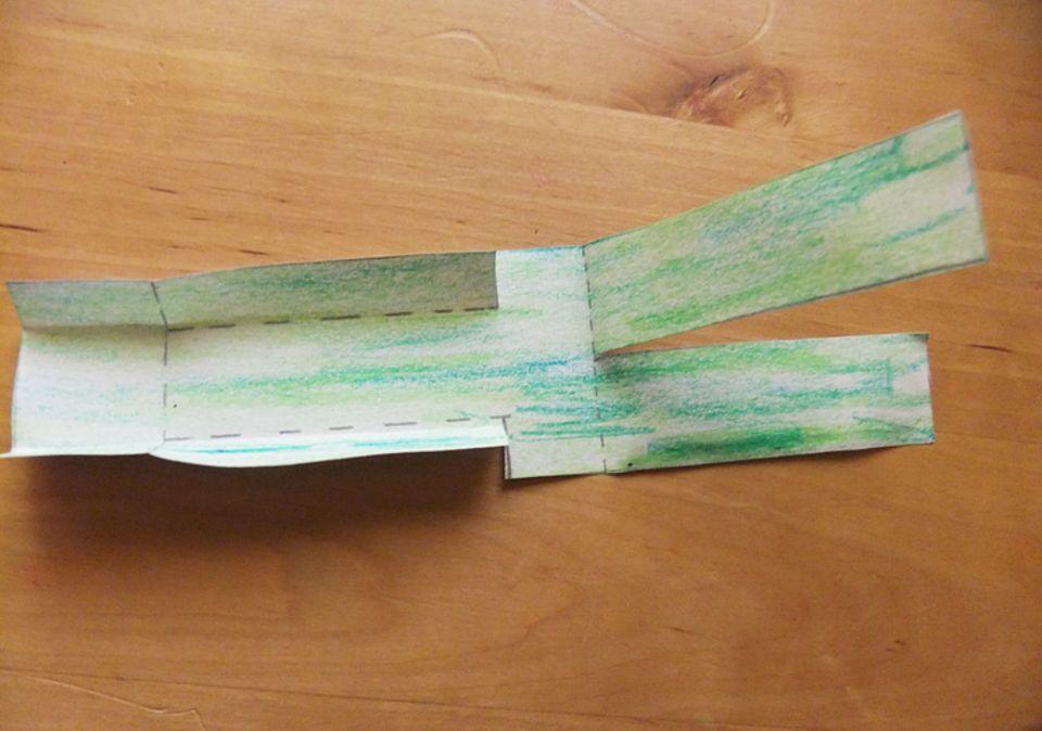 Buchtipp: Schneide die gezogenen Linien ein, dann knicke das Papier an den gestrichelten Linien. Nun sieht deine Bastelei so aus.