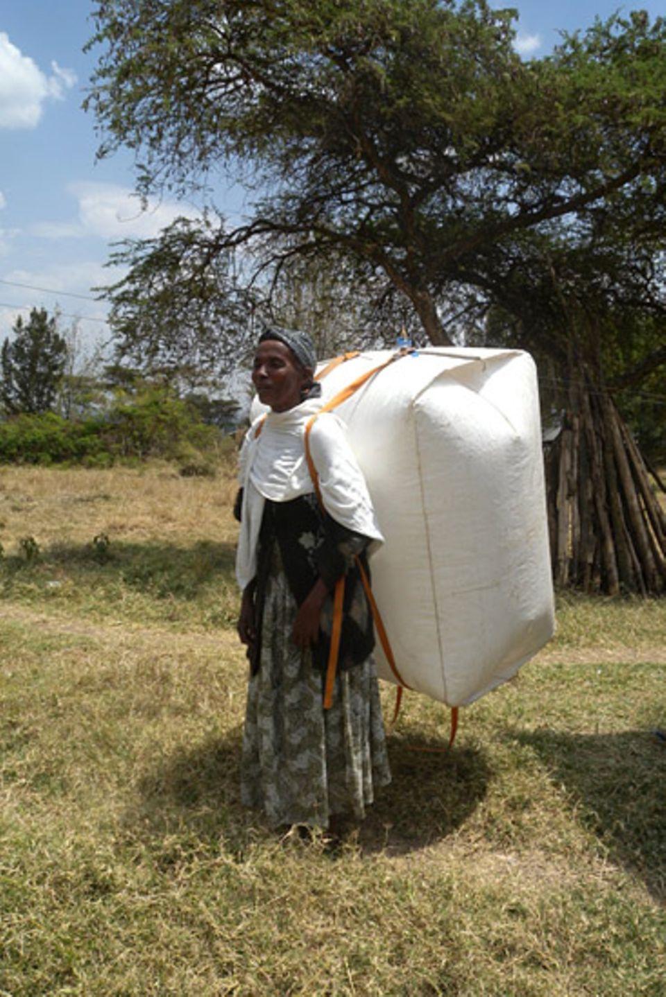 Biogas: Voluminös, aber nicht schwer: Dorfbewohnerin mit Biogasrucksack