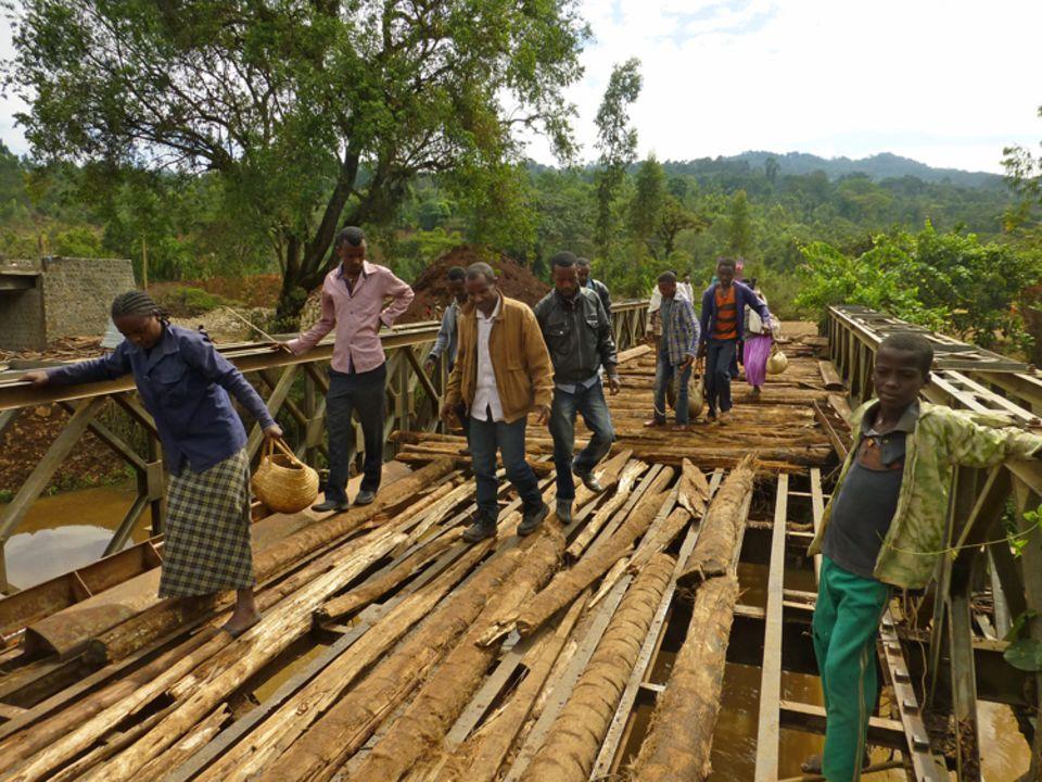 Bevor er die Überquerung mit dem Fahrzeug versucht, prüft der Leiter der Farmers Union Frehiwet Getahun (Mitte), die Stabilität der alten Brücke