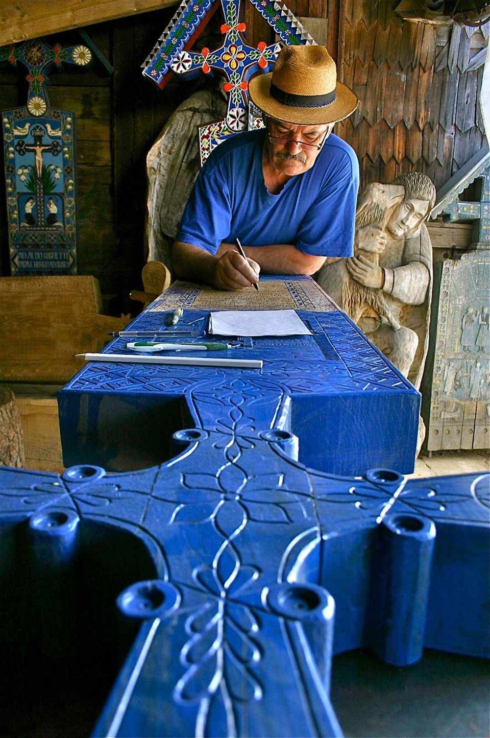 """Dumitru Pop fertigt die kunstvollen Kreuze für den Friedhof von Sâpânta. Grundlage für seine ins Holz gemeißelten Texte und Bilder ist das typische, leuchtende """"Blau von Sâpânta"""""""