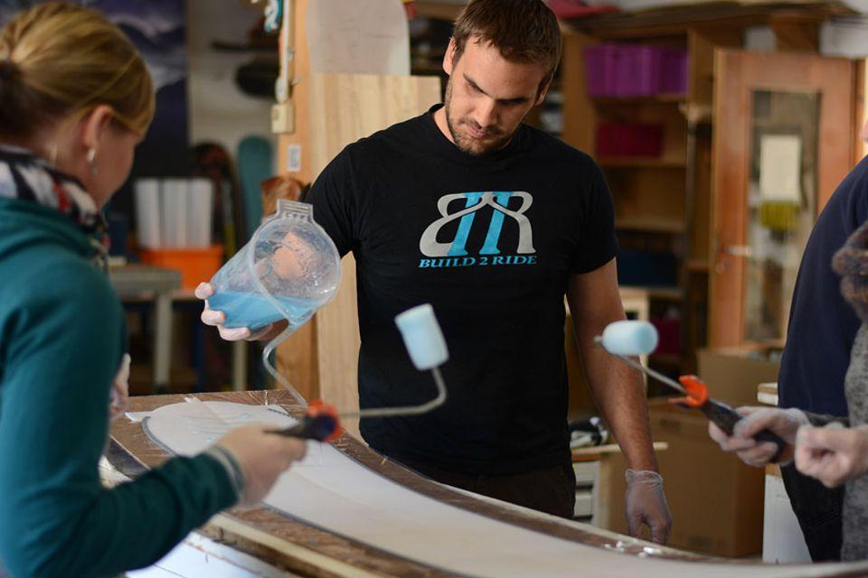Garmisch-Partenkirchen: Axel Forelle, Mitbegründer von Build2Ride, hilft den Teilnehmern beim Harz auftragen. Doch nur die wenigsten Handgriffe übernehmen die Profis selbst. Sie erklären jeden Schritt so einfach wie möglich und überlassen den Rest den Teilnehmern - für das Erfolgserlebnis am Schluss