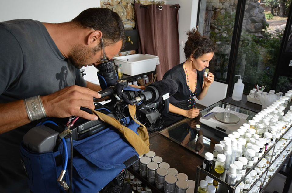 Kameramann Ralph Wilhelm beobachtet Parfumeurin Delphine Thierry beim Verwiegen einer Duftformel