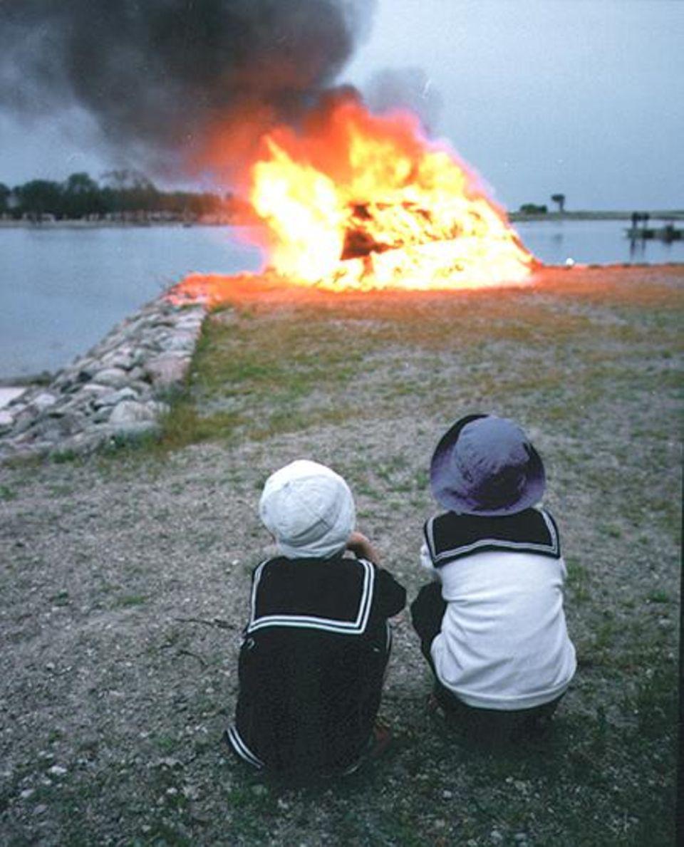 Johannisfeuer: Kinder warten im Hafen von Kuressaare bis das Feuer auf kleiner Flamme brennt. Dann dürfen sie darüber hinwegspringen