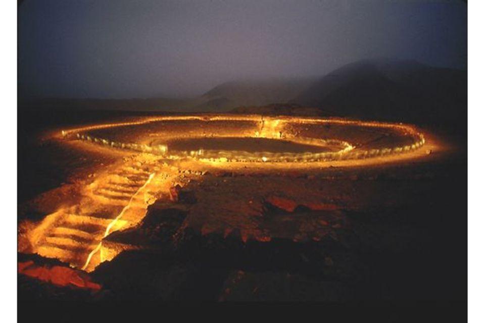 Peru: Fackeln beleuchten das Ruinen-Rund des Amphitheaters von Caral