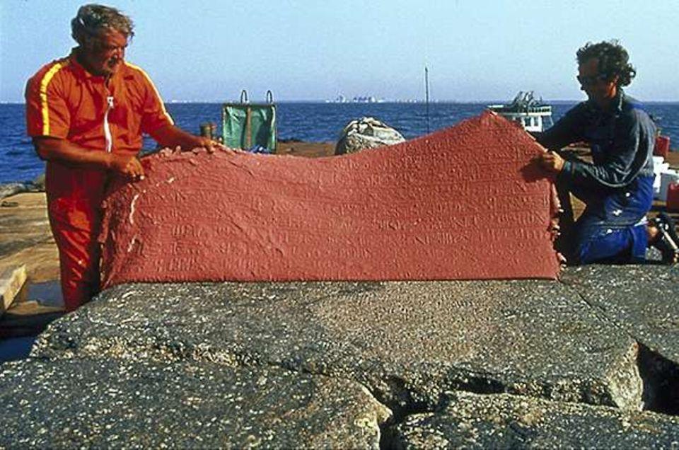 Nach dem Trocknen wird rotes Silikon von einer gefetteten Stele abgezogen - mit einem Relief der Inschriften auf dem Granit