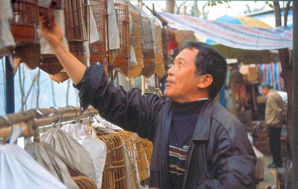 Herr Huang auf seinem Stand auf dem Vogelmarkt in Guangzhou. Nur wenige Vogelarten kommen in China in den Handel, sei es, weil ihr Gesang besonders schön ist oder sich diese Tiere in der Käfighaltung bewährt haben