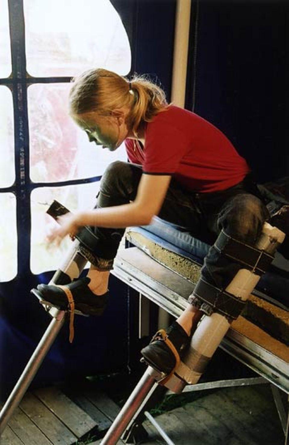 Kurz vor der Vorstellung schnallt sich ein Mädchen Stelzen an die Beine