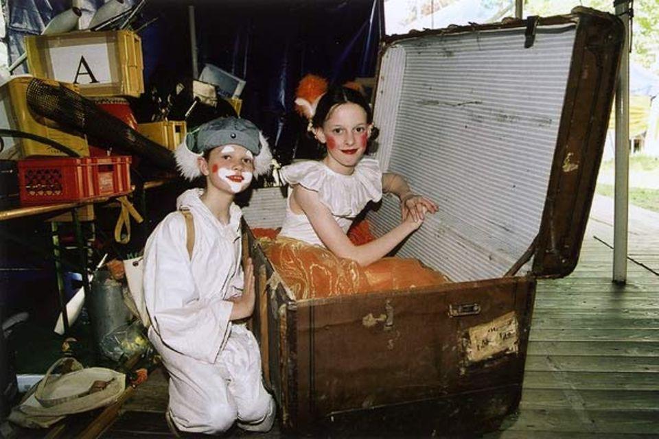 Hinter der Bühne stapeln sich Schachteln, Koffer und Kästen