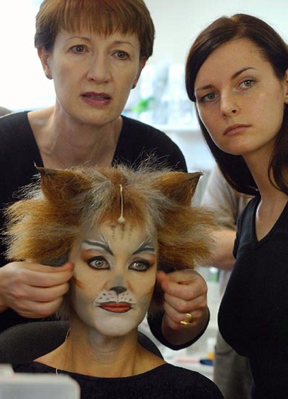 """Beruf: Ganz vorsichtig setzt die Maskenbildnerin der """"Katze Grizabella"""", die von Cornelia Drese gespielt wird, die Perücke auf - damit die Schminke nicht verschmiert wird. Bis zum 30. Januar 2004 kann man sich CATS noch im Theater am Potsdamer Platz in Berlin anschauen"""