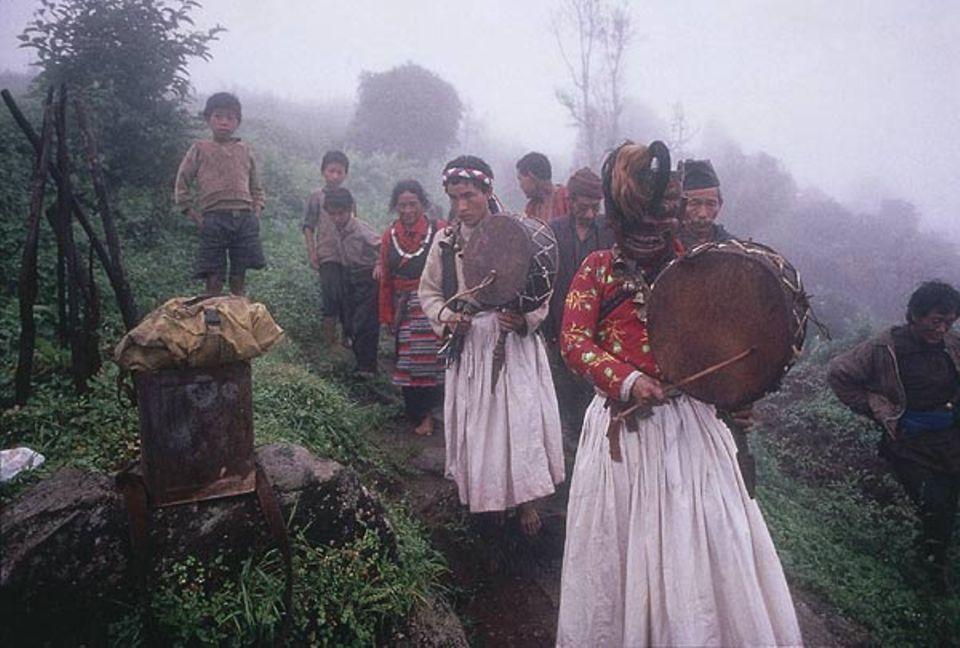 """Einmal im Jahr zieht Mingmar unter dem Antlitz des Urschamanen Shiva durchs Dorf. Die rituell """"belebte"""" Maske des Gottes soll es spirituell reinigen"""