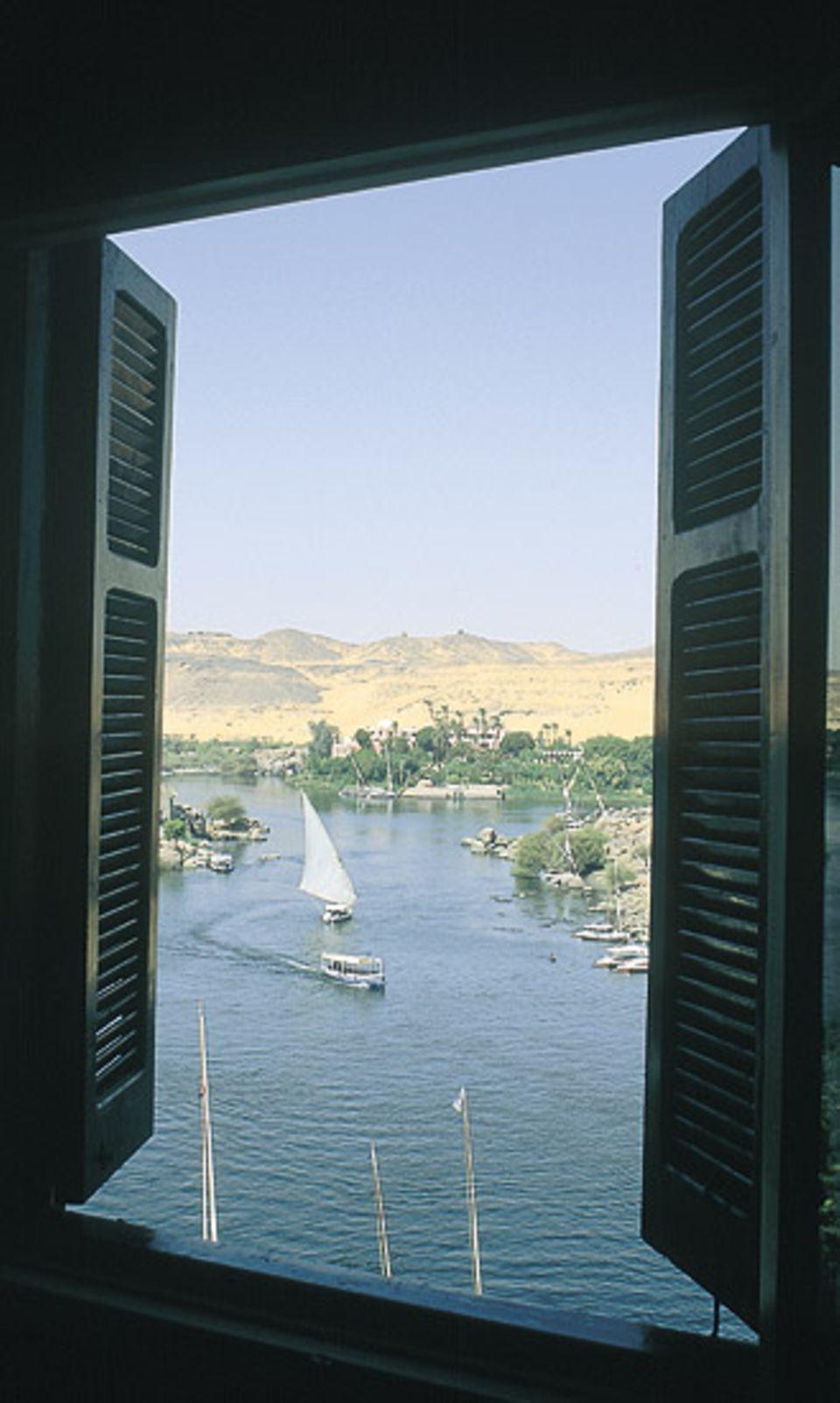 """Wasser, Boote und Wüste in Assuan - zeitgenössischer Blick aus einem Fenster des Hotels """"Old Cataract"""""""