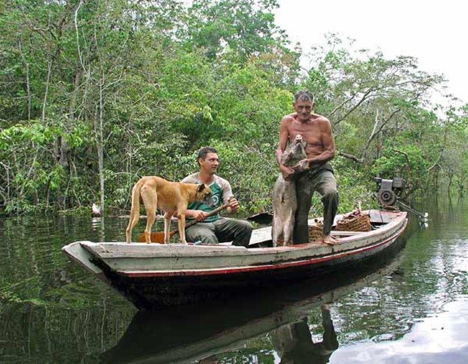 Einheimische Jäger mit ihrer Beute, einem Riesen-Pekari