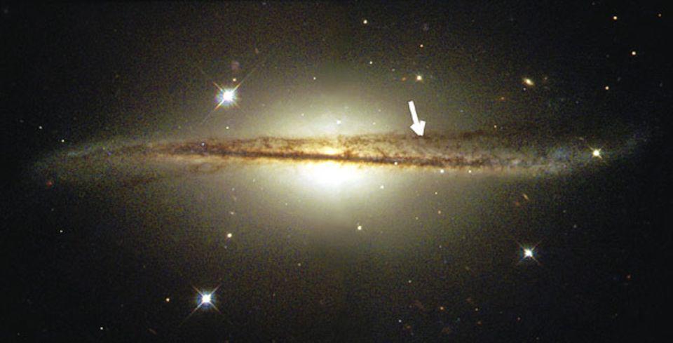 Galaxien: Ein Arm der Spiralgalaxie ist nach oben gezogen (Pfeil), möglicherweise durch einen Zusammenstoß mit einer anderen Galaxie
