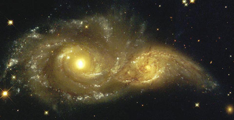 Galaxien: Die Galaxie (oben links) hat das Sternensystem angezogen und lässt es nicht mehr los