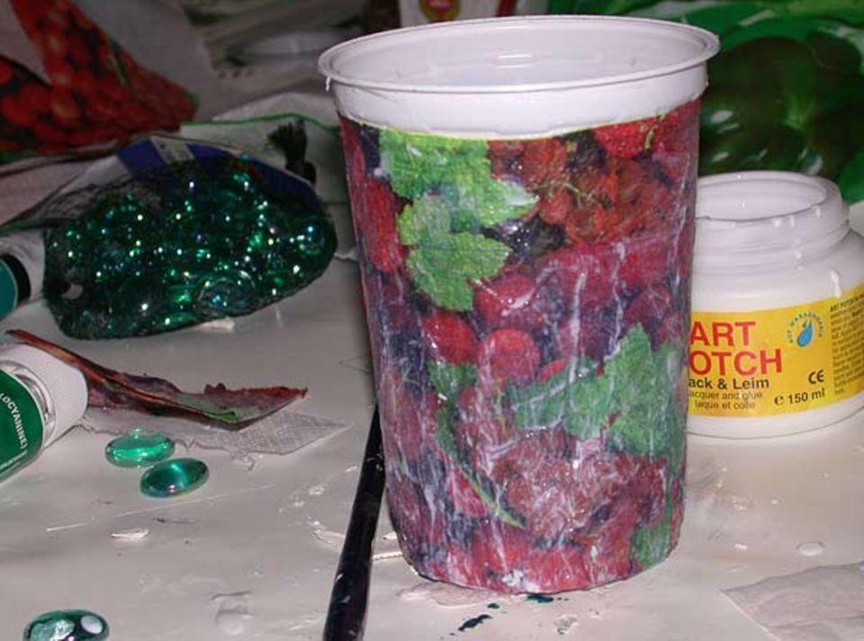 Upcycling: Die Serviette wird mit Lack-Leim auf die Dose geklebt