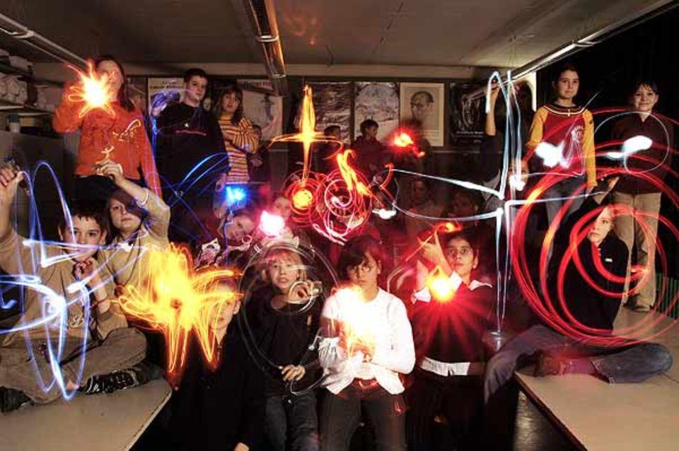 Mit Taschenlampen zaubern die Schüler einen bunten Sternenhimmel