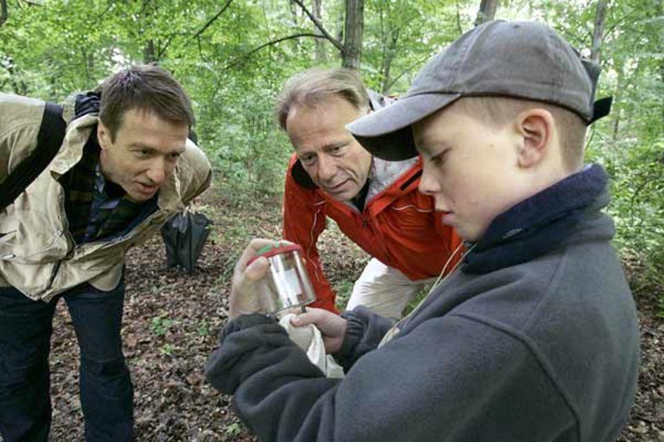 """Der Organisator des """"Tages der Artenvielfalt"""" Tom Müller und Bundesumweltminister Trittin betrachten gespannt ein Insekt, das ein Schüler mit seiner Becherlupe eingefangen hat"""