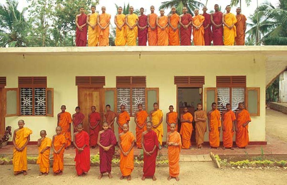 In einer Klosterschule bei Colombo posieren Novizen und ihre Lehrer vor und auf dem Klassenzimmer
