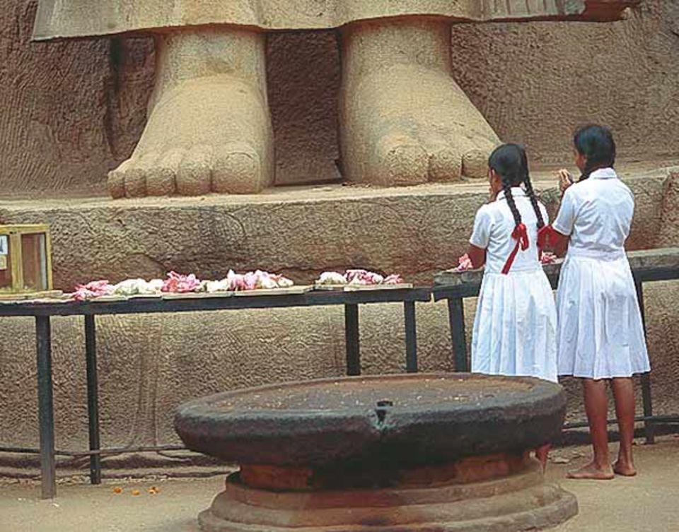 Schulmädchen beten zu Füßen der über 13 Meter hohen Buddhastatue von Aukana