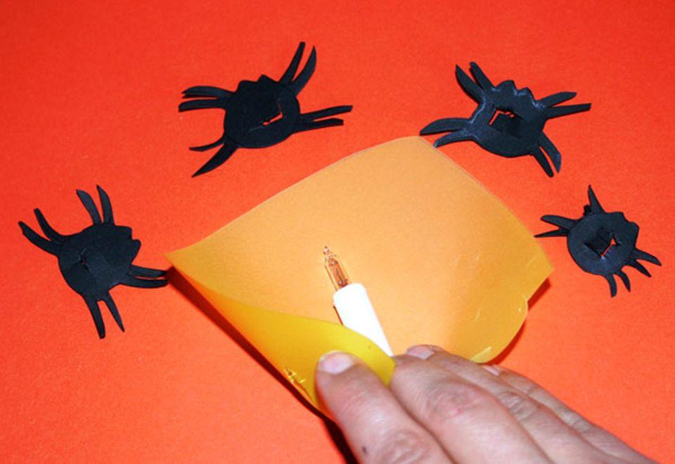 Halloween: Das Transparentpapier lässt sich ganz einfach an den Lämpchen befestigen
