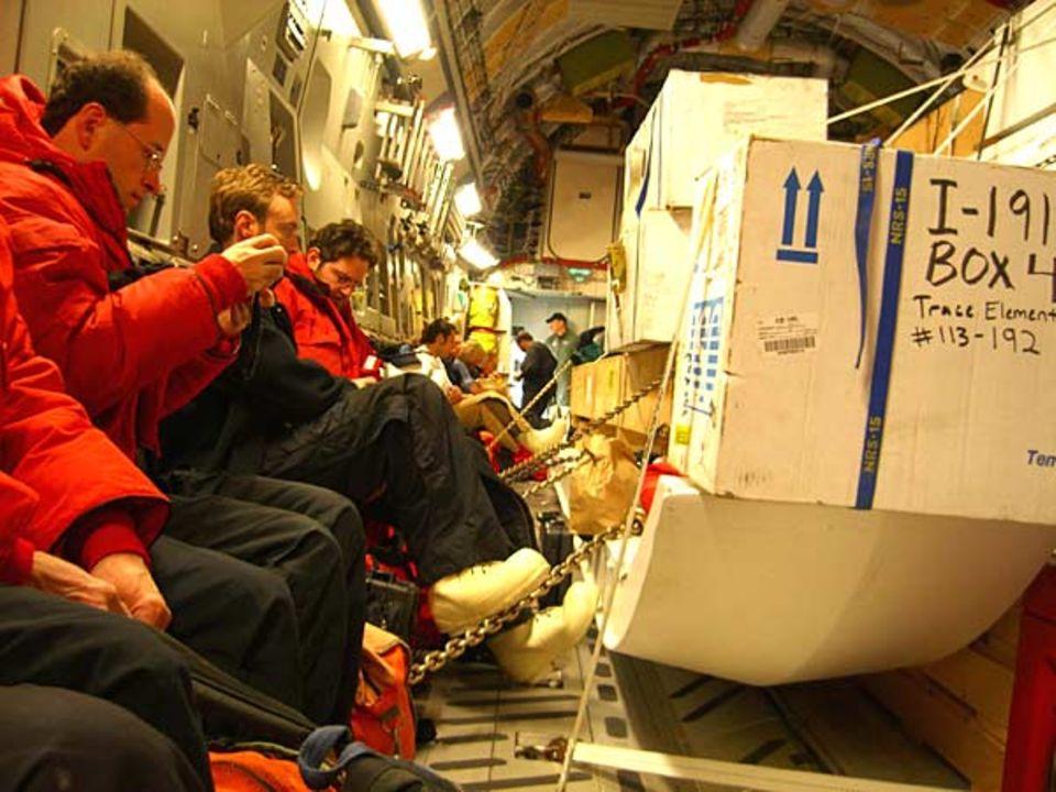 Eingepackt in mehrere Schichten Polarkleidung sitzen die Passagiere zwischen turmhohen Paletten mit Baumaterial, Chemikalien und Bananen