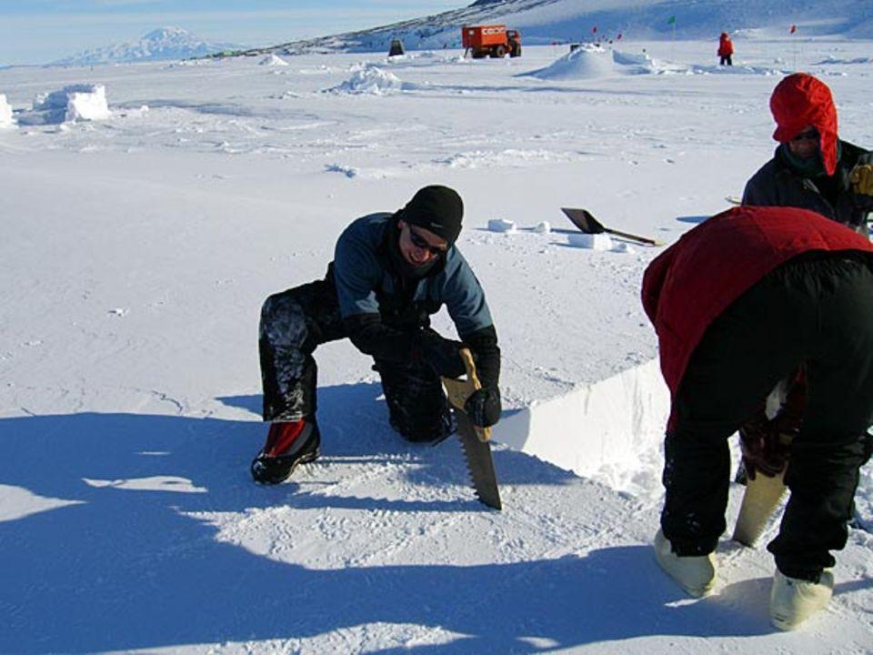 Aus dem vom Wind steinhart planierten Schneeboden sägt GEO-Redakteru Lars Abromeit passgenaue Blöcke für eine Schutzmauer heraus
