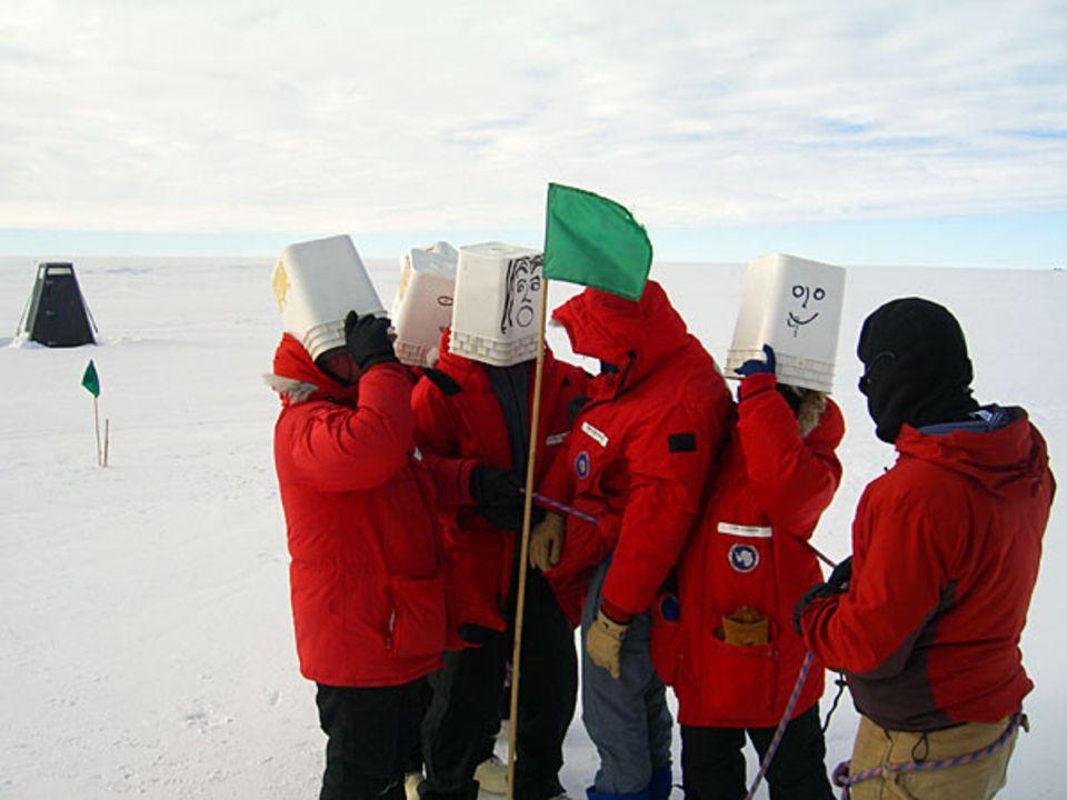"""Simulation eines """"White Out"""": Mit weißen Plastikeimern über den Kopf suchen die Campteilnehmer im Eisfeld nach einem Vermissten"""