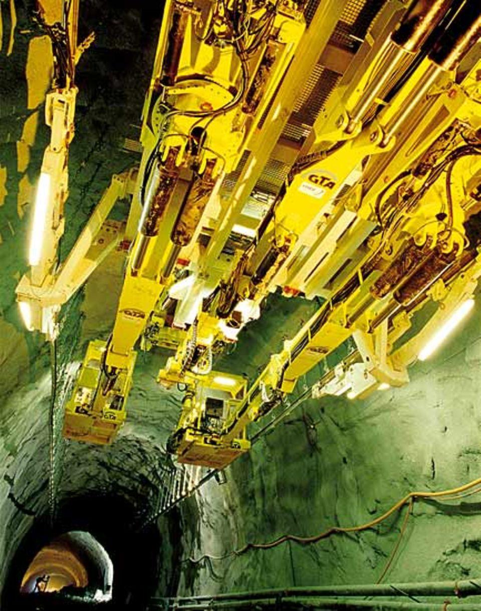 """Die Streckenausbaumaschine ist ein """"Mädchen für alles"""": sie führt zwei Arbeitskörbe und einen Spritzbetonroboter mit sich und transportiert Stahlträger zum Sichern der Tunnelröhre"""