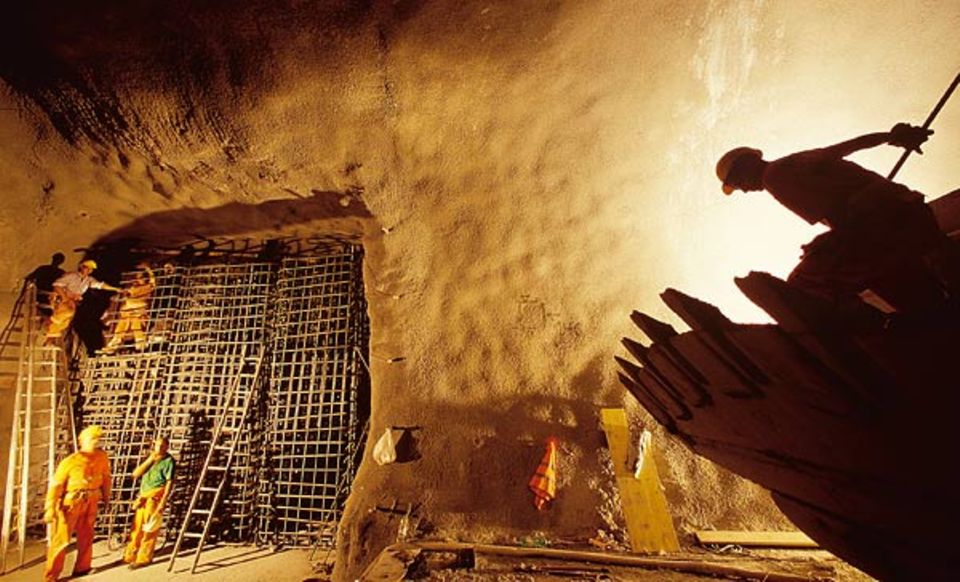 Um die Seitenwände des Tunnels zu befestigen, ziehen Arbeiter Armierungsgitter ein