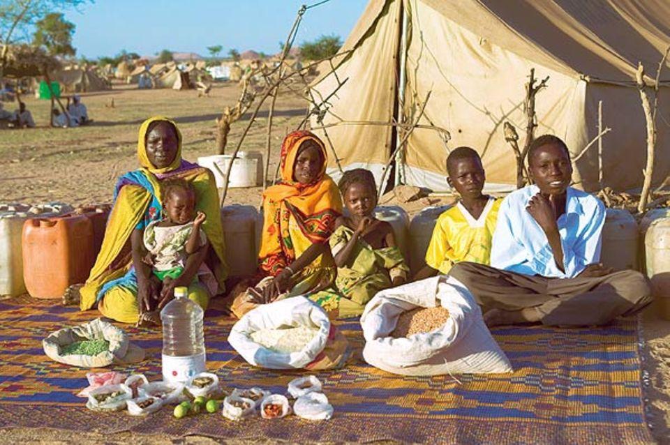 Hirse und Mais sind die Hauptnahrungsmittel für Abdel Kerim (rechts) und seine Familie, dazu ein paar Früchte, Öl und Zucker. Das ist nicht viel - aber besser als zu hungern