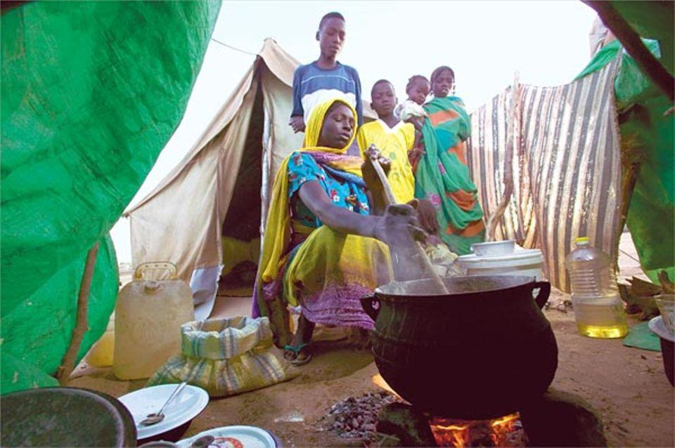 """Einheitsbrei: Morgens, mittags und abends rührt Abdel Kerims Mutter """"Aiysch"""" an, auf einem offenem Feuer direkt vor dem Zelt, in dem die Familie im Lager lebt"""