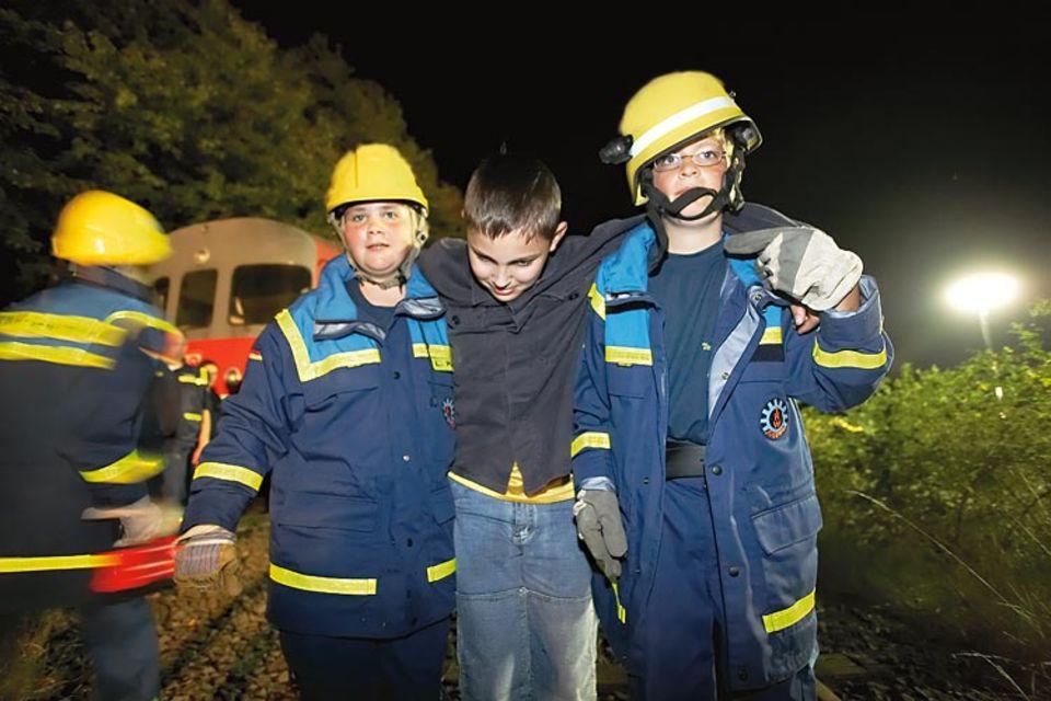 Laura und Lukas schleppen einen kranken Jungen zum Krankenwagen