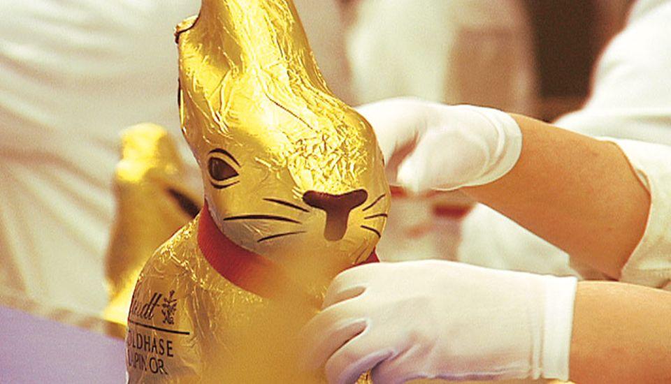 Hinter den Kulissen: Fast fertig! Der Schokohase ist in goldenes Aluminiumpapier gewickelt und bekommt sein Glöckchen um den Hals.