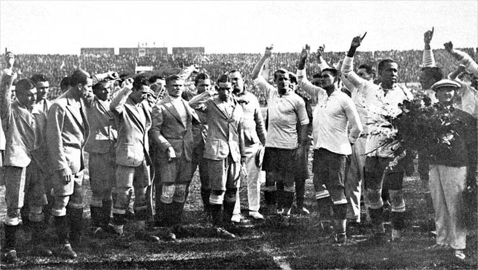 Fußball-WM-Serie in drei Teilen: Vor dem Endspiel der Fußball-Welltmeisterschaft am 30.07.1930 in Montevideo, Uruguay: Die Fußball-Nationalmannschaften von Argentinien (l) und Uruguay begrüßen winkend die Zuschauer